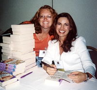Lisa and a fan at a table where Lisa is signing books